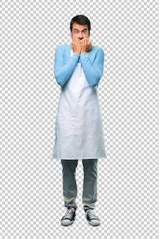 L'uomo che indossa un grembiule che copre la bocca con entrambe le mani per dire qualcosa di inappropriato.
