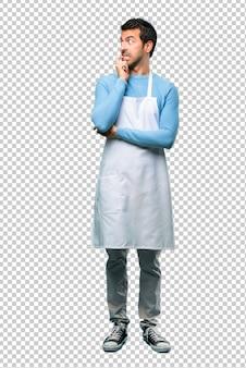 Uomo che indossa un grembiule che ha dubbi e con l'espressione faccia confusa mentre alzando lo sguardo.