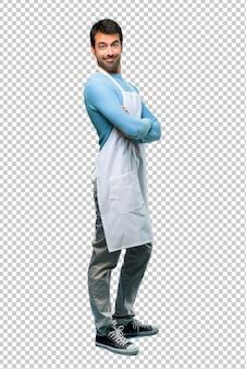 L'uomo indossa un grembiule tenendo le braccia incrociate in posizione laterale mentre sorride.