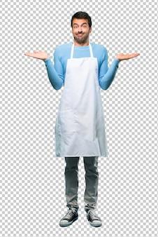 L'uomo che indossa un grembiule che fa gesto poco importante e dubita sollevando le spalle
