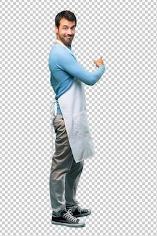 Uomo che indossa un grembiule che punta indietro con il dito indice che presenta un prodotto da dietro