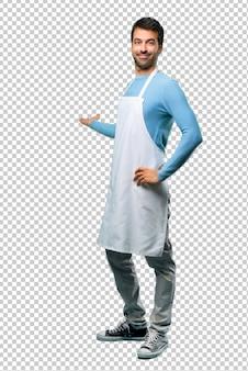 Uomo che indossa un grembiule che punta indietro con il dito indice che presenta un prodotto