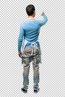 Uomo che indossa un grembiule che punta indietro con il dito indice