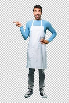 Uomo che indossa un grembiule che indica il dito sul lato e che presenta