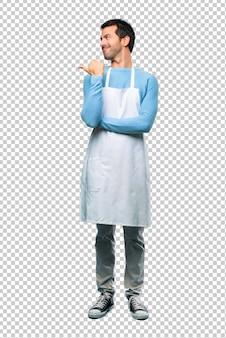 Uomo che indossa un grembiule che punta verso il lato con un dito per presentare un prodotto o un'idea
