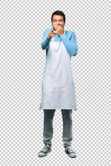 Equipaggi l'uso del grembiule che indica con il dito qualcuno e che ride molto mentre copre la bocca