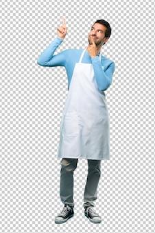 L'uomo indossa un grembiule che punta con il dito indice una grande idea e guardando in alto