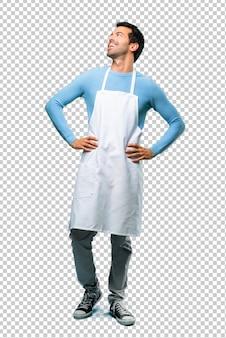 Uomo che indossa un grembiule in posa con le braccia all'anca e ridendo