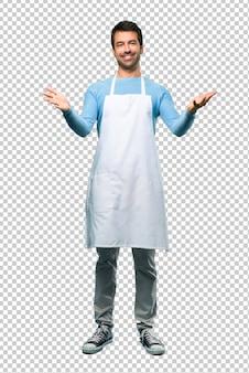 L'uomo indossa un grembiule che presenta e invita a venire con la mano. felice che tu sia venuto