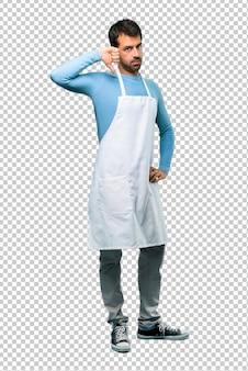 L'uomo che indossa un grembiule che mostra il pollice giù firma con l'espressione negativa. espressione triste