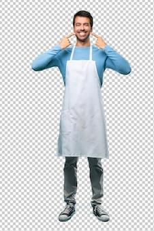 Uomo che indossa un grembiule sorridente con un'espressione felice e piacevole