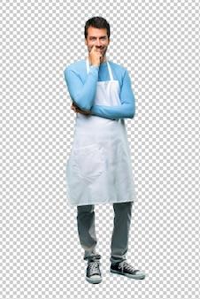 Uomo che indossa un grembiule sorridente con un'espressione dolce