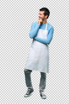 L'uomo indossa un grembiule in piedi e guarda di lato con la mano sul mento
