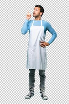 Uomo che indossa un grembiule in piedi e pensando un'idea che punta il dito verso l'alto