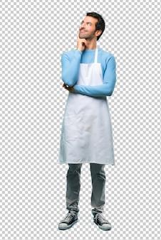 Uomo che indossa un grembiule in piedi e pensando un'idea mentre alzando lo sguardo