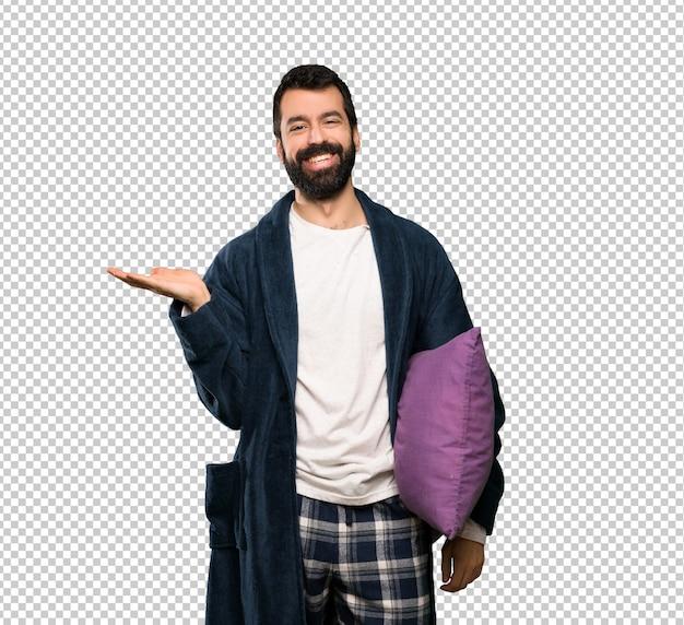 Uomo con la barba in pigiama con copyspace immaginario sul palmo per inserire un annuncio