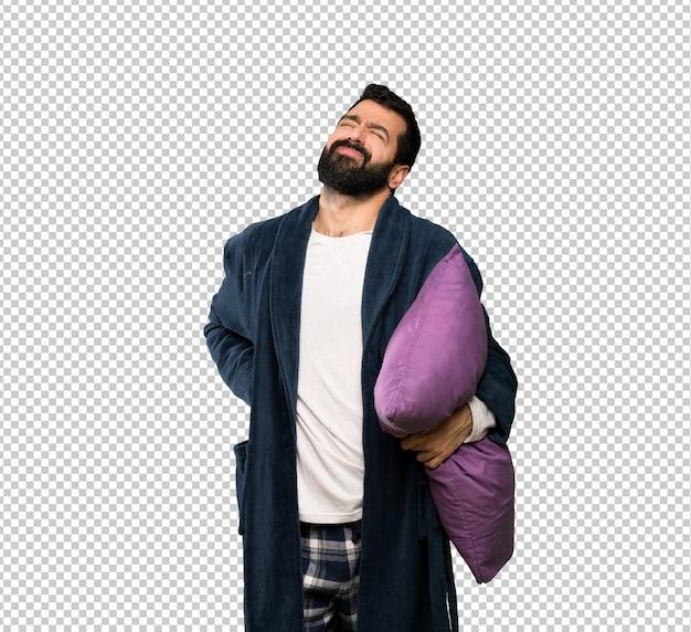 Uomo con la barba in pigiama che soffre di mal di schiena per aver fatto uno sforzo