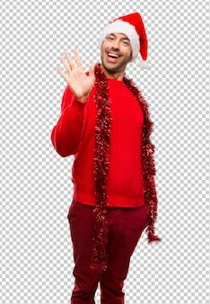 Uomo con i vestiti rossi che celebra le feste di natale che salutano con la mano con l'espressione felice