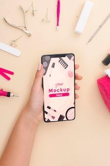 Disposizione degli elementi per manicure con mock-up del telefono