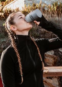 Donna del colpo medio che beve dalla latta