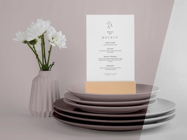 Modello di menu con supporto in legno e vaso di fiori