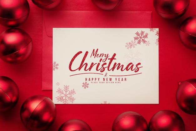 Cartolina d'auguri di buon natale e mockup di busta con palle di natale