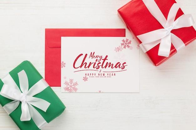 Biglietto di auguri di buon natale e mockup di busta con confezione regalo