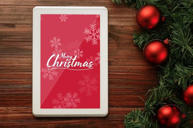 Mockup di computer tablet di buon natale con decorazioni di foglie di pino