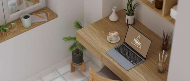 Spazio di lavoro minimalista accogliente sala di lavoro laptop schermo vuoto con decorazioni su tavolo di legno wooden