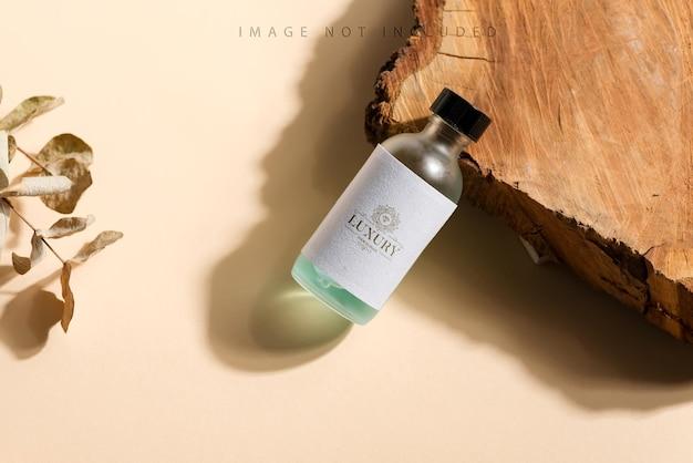 Mock up bottiglia su un taglio di legno e superficie beige
