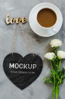 Manichino del biglietto di auguri. il cuore vuoto del bordo di gesso ha modellato con la tazza e i fiori di caffè.
