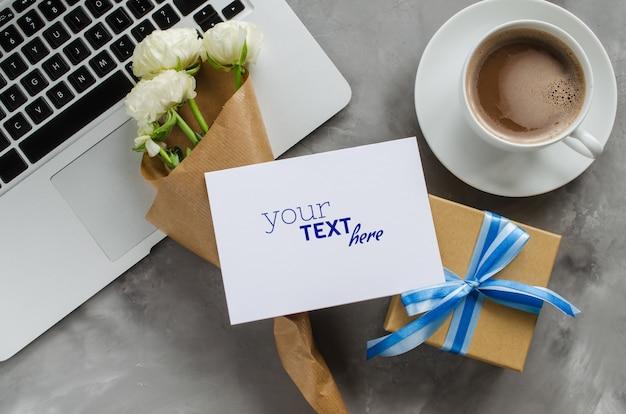 Manichino di biglietto di auguri con computer portatile, confezione regalo, caffè del mattino e fiori.