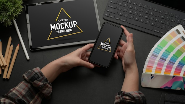 Mock up smartphone sul tavolo da lavoro con mock up tablet, tastiera e materiali di design
