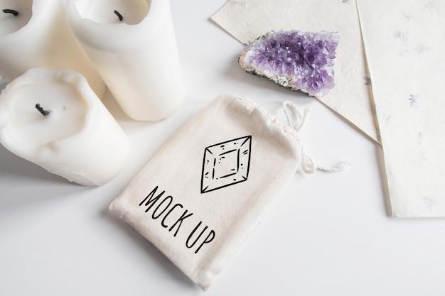Manichino di borsa di cotone tarocchi, ametista e candele su sfondo bianco