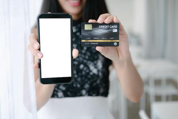 Modello di bella donna che tiene la carta di credito che compera online con lo smartphone sui siti web online