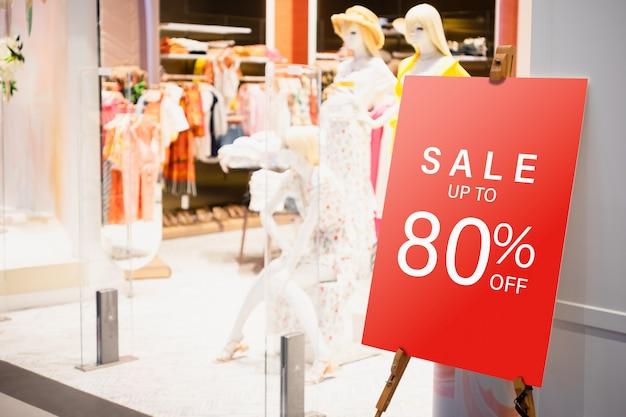 Stadt del tabellone per le affissioni del modello davanti al negozio di vestiti femminile