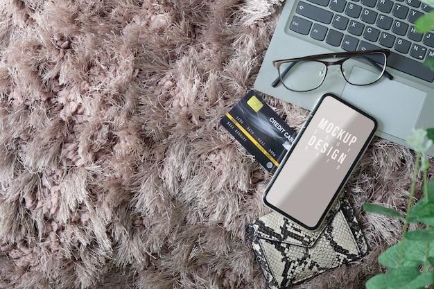 Mockup del telefono cellulare schermo vuoto con laptop, occhiali e carta di credito