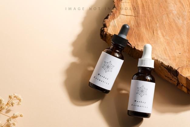 Flaconi per la cosmetica mockup con un contagocce su un taglio di legno e una superficie beige con luce solare intensa e ombre dure.