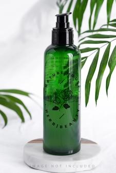 Mockup bottiglia di plastica verde con foglie tropicali di palma sempreverdi copia spazio