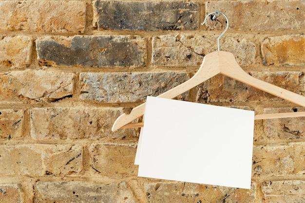 Mockup di biglietto di auguri su una gruccia sul muro di mattoni