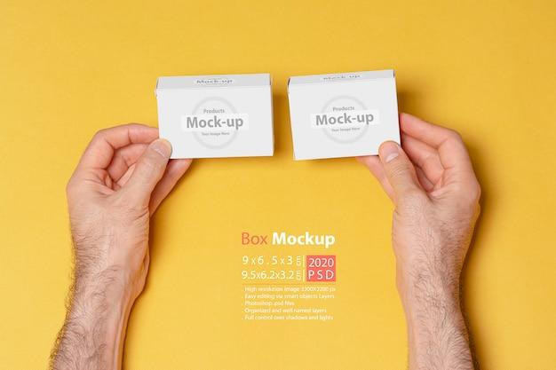 Mockup di mani confrontando due scatole di pillole