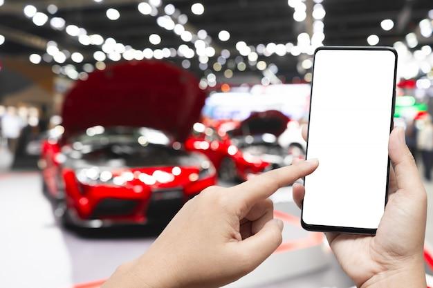 Immagine del modello della mano che tiene il cellulare dello schermo in bianco e che indica lo smart phone con fondo vago dell'esposizione delle nuove automobili