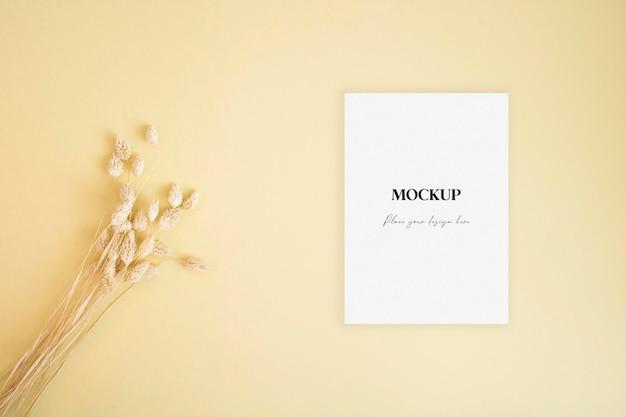 Carta di invito mockup con erba secca su sfondo giallo