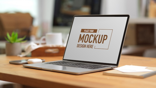 Computer portatile mockup sulla tavola di legno con forniture per ufficio e cancelleria