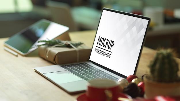 Computer portatile di mockup sulla tavola di legno con lo smartphone