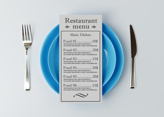 Il modello del menu si trova sopra un piatto con un coltello e una forchetta Psd Premium
