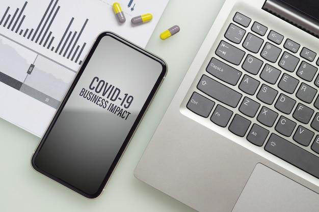 Telefono cellulare del modello con il computer portatile per rischio finanziario covid 19 di affari.