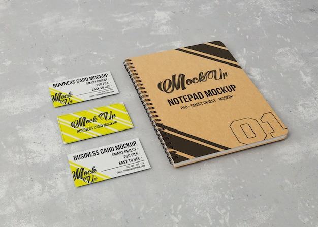 Blocco note mockup e tre biglietti da visita