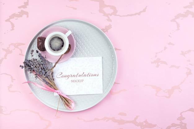 Modello sulla nota di carta con la tazza di caffè e la lavanda secca sul piatto sul rosa