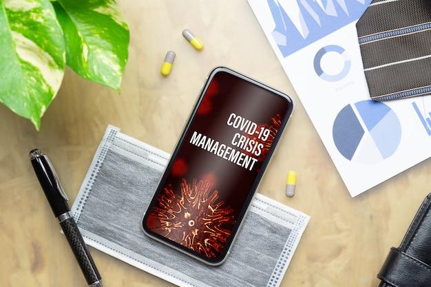 Smartphone del modello per il concetto del fondo della gestione di crisi di covid-19.